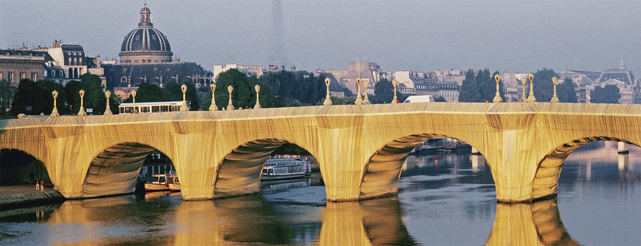 The Pont Neuf Wrapped, Paris, 1975-85. Le plus ancien pont existant de Paris apparaît ici couvert de polyamide couleur « pierre calcaire dorée », fin septembre 1985, devant le dôme de l'Institut de France et la tour Eiffel.
