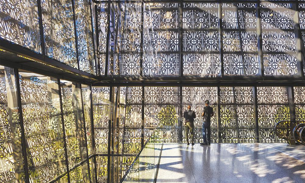 Le revêtement extérieur en panneaux ajourés en alimunium enduits de bronze filtre la lumière du jour et crée un jeu complexe d'ombres à l'intérieur.