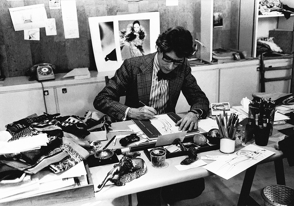 Yves Saint Laurent dessine dans son studio, Paris 1976. © Musée Yves Saint Laurent Paris / Guy Marineau