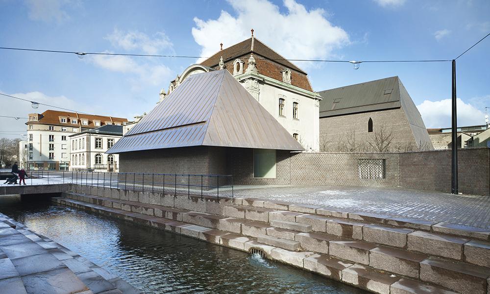 Musée Unterlinden, Colmar. Après la rénovation du musée, deux groupes de bâtiments se font face sur une place. Une nouvelle structure en brique pour les expositions (Ackerhof) et une petite maison sont reliées aux anciennes structures au niveau souterrain.