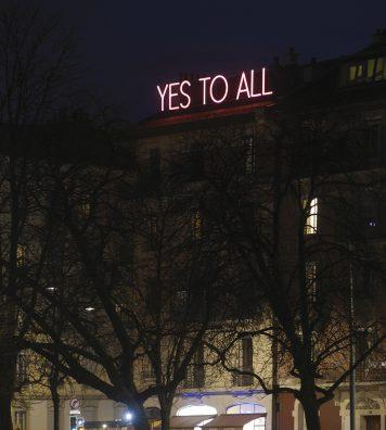 « YES TO ALL ». Lisible de tous les points de vue de la plaine de Plainpalais, le message en néon blanc entouré d'un halo rose proposé par Sylvie Fleury nous enjoint à l'optimisme.