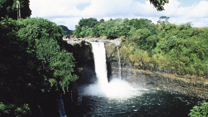 Rainbow Falls à Hawaii. La cascade est enserrée dans la roche et la jungle.