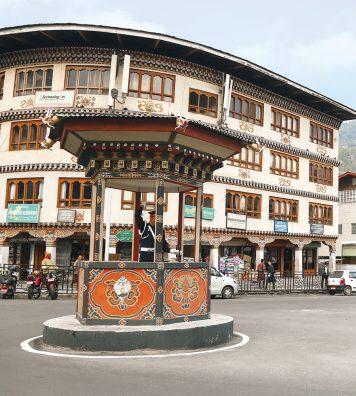 Heure de pointe sur un carrefour de Thimphu. Malgré l'absence d'embouteillages, un agent de la circulation régule le trafic, à l'abri dans une guérite en bois sculpté.