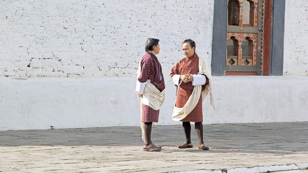 Bhoutanais portant le costume traditionnel, le gho, qui ressemble à une longue robe arrivant aux genoux.
