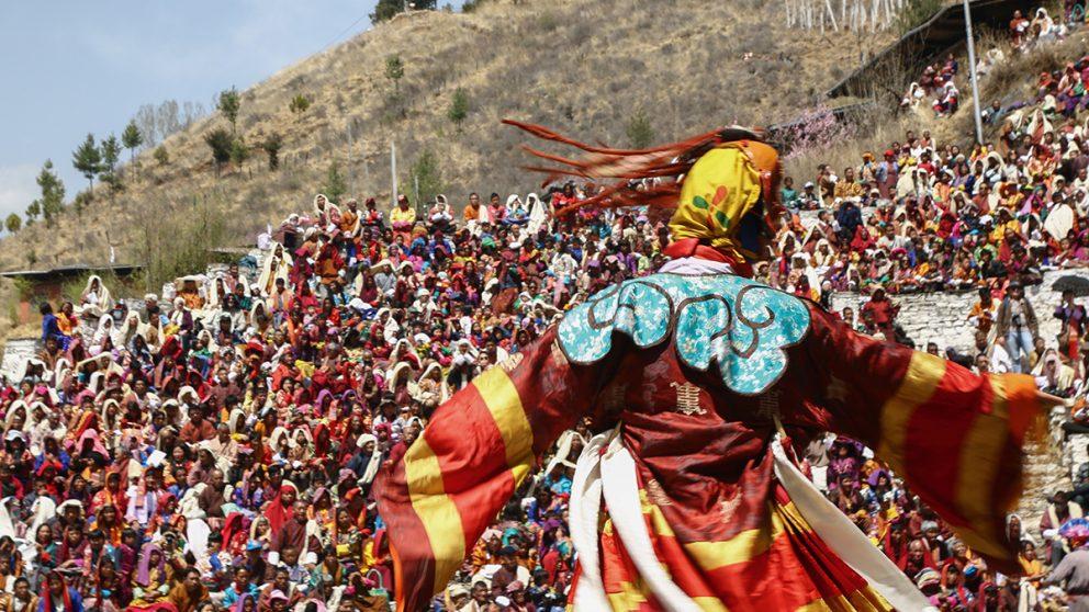 Scène de danse lors du festival annuel de Paro au Bhoutan. Un danseur mime un personnage divin devant une foule d'habitants.