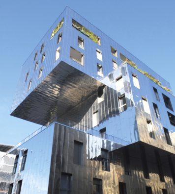 La darse, le bassin rectangulaire au cœur de Confluence. Un espace public majeur du quartier, desservi par une navette. En bas : un immeuble de logements mixtes (libres et sociaux), commerces en rez, de Massimiliano Fuksas (2010).