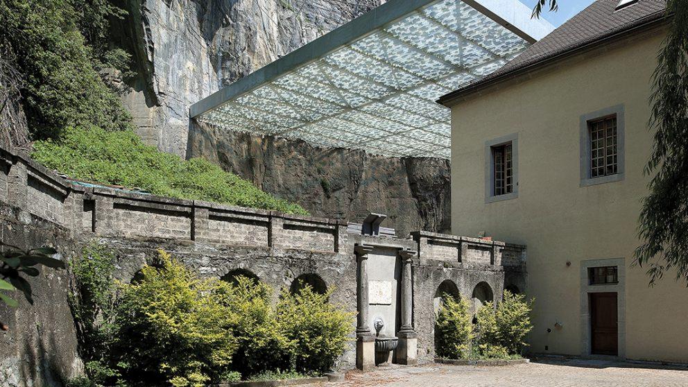 Vue depuis la Cour Saint-Joseph. La couverture s'insère entre la falaise et les bâtiments de l'Abbaye.