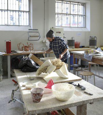 Atelier du CERCCO. Un étudiant au travail dans les espaces lumineux du centre d'expérimentation et de réalisation en céramique contemporaine de l'école.