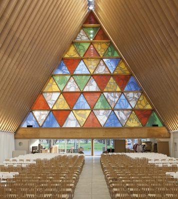 Cardboard Cathedral à Christchurch, en Nouvelle-Zélande. Sous la nef de la cathédrale, les verres triangulaires font écho à la forme du bâtiment. Le mobilier a aussi été dessiné par Shigeru Ban.