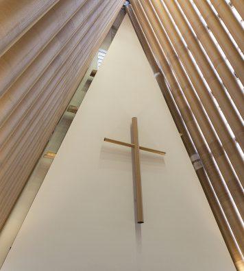 Cardboard Cathedral à Christchurch en Nouvelle-Zélande. Au-dessus de la croix, la structure en tubes de papier du toit est complètement visible, ce qui met un accent sur le caractère éphémère du bâtiment, mais qui ne nuit nullement à sa solennité.
